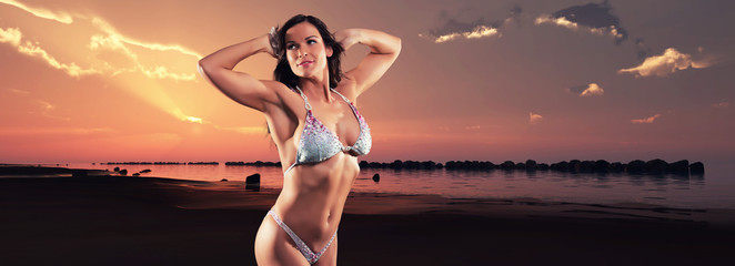 Muscled fitness woman wearing bikini. On the beach at sunset. Pa