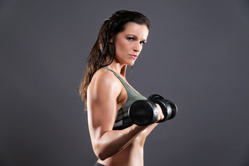 Fitness woman weight lifting with dumbbells. Wearing camouflage