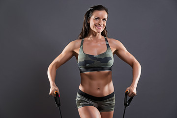 Fitness woman exercising with elastics. Wearing camouflage sport