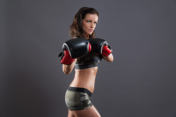 Tough fitness woman with boxing gloves. Wearing camouflage sport