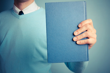 Young man holding a big book