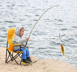 Little boy catching little fish. Happy vacations concept.