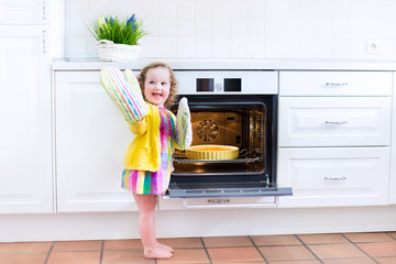 Sweet toddler girl with an apple pie in the oven