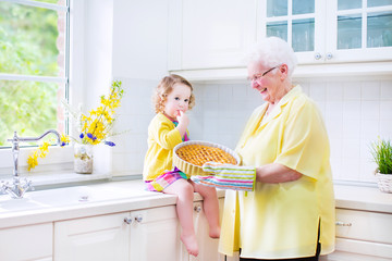 Loving grandmother with granddaughter baking pie in kitchen