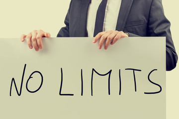 Businessman holding up a sign saying - No Limits