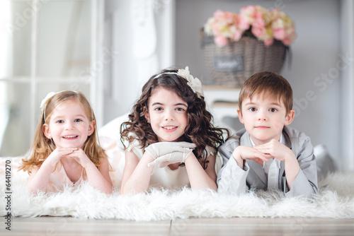 Leinwanddruck Bild tres niños en la fiesta,tumbados,