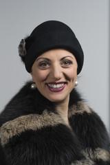 donna sorridente con cappello scuro e pellicciotto
