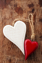 two wooden hearts, red and white on old wooden background