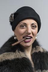 donna con sigaro cappello scuro e pellicciotto