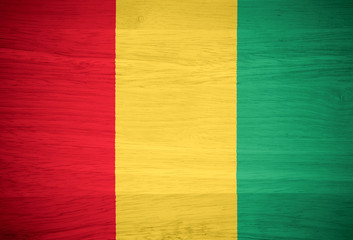 Guinea flag on wood texture