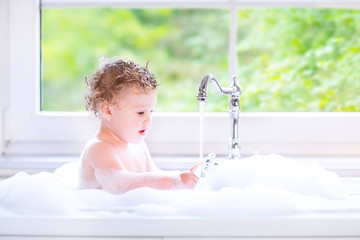 Sweet baby girl playing with water and foam in big kitchen sink
