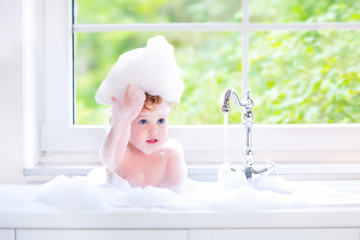 Little baby girl playing with water and foam in big kitchen sink