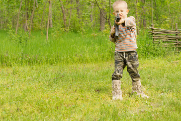 Little boy pointing an automatic weapon