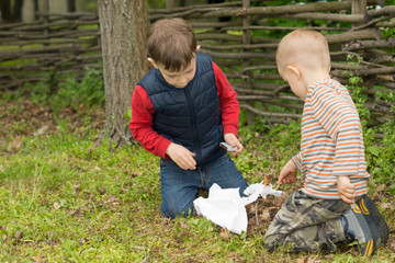 Two small boys trying to light a fire in a field