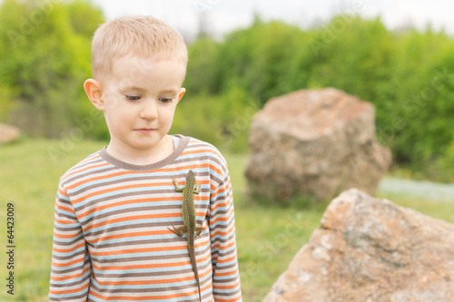 Cute little boy with a lizard on his chest