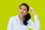 Poor memory. Confused woman scratching head green background
