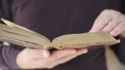 man turns pages of old book