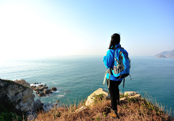 woman hiker stand seaside enjoy the view