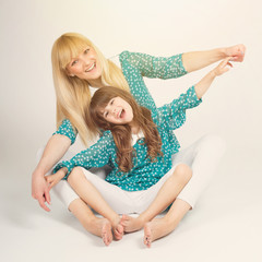 Cute mother and daughter smiling and playing together