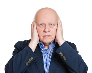 Hear no evil. Senior man covers his ears, on white background