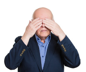 Senior citizen covers his eyes with hands, see no evil concept
