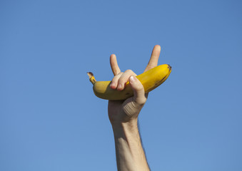 Hand holding a banana and making the evil sign