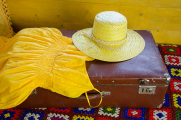 yellow dress and straw hat lying on old suitcase
