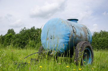 Blue water cistern drink for farm animal in meadow