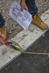 road paint worker holding plans and measuring tape