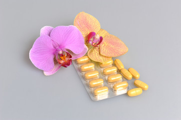 Film-coated tablets with two orchid flowers on gray