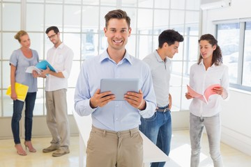 Casual boss smiling at camera in front of business team