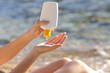 Woman hands putting sunscreen from a bottle on the beach - 64432837