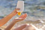 Woman hands putting sunscreen from a bottle on the beach - Fine Art prints
