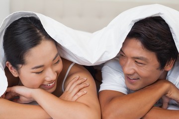 Happy couple lying on bed together under the duvet