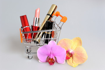 Makeup in pushcart with orchid flowers on gray