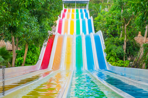 Colorful waterslides in water park - 64435262