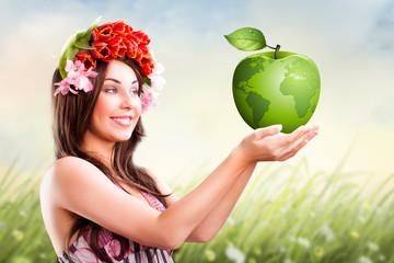 junge attraktive Frau hält grünen Apfel-Globus