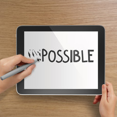 hand changing the word impossible to possible with stylus eraser