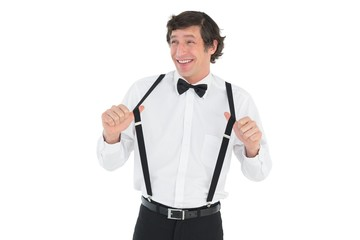 Happy groom stretching suspenders