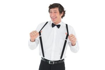 Happy groom stretching suspenders