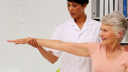 Nurse showing elderly patient how to exercise her injured arm