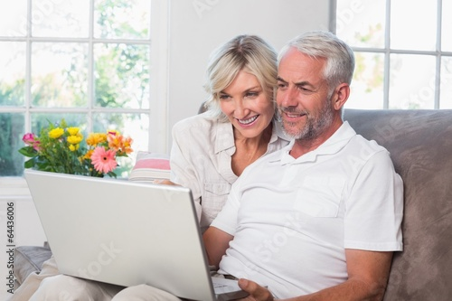 Mature couple using laptop at home - 64436006