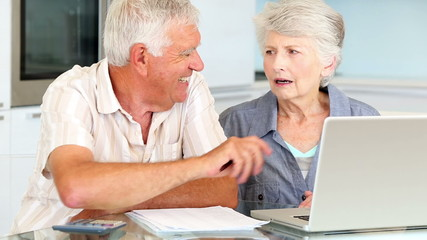 Senior couple using laptop to pay their bills