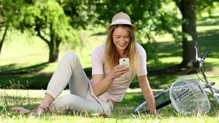 Pretty girl using smartphone beside her bike in the park
