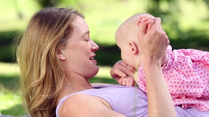 Happy mother playing with her baby girl in the park