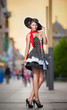 Fashionable lady wearing elegant dress, black hat and red scarf