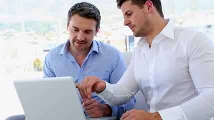 Businessmen working together on laptop