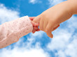 Two children holding hands on sky background.