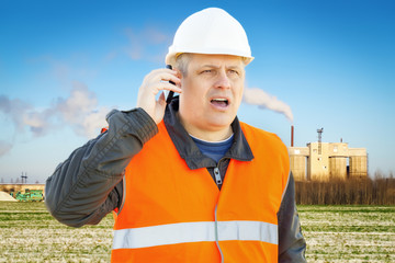 Engineer with cell phone near the factory