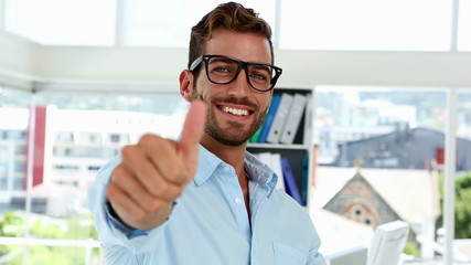 Happy designer giving thumbs up to camera